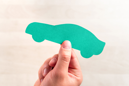 Car sale or loan, auto insurance, driving school or vehicle inspection and check up concept. Buying new or used automobile. Hand holding a cardboard paper shape.