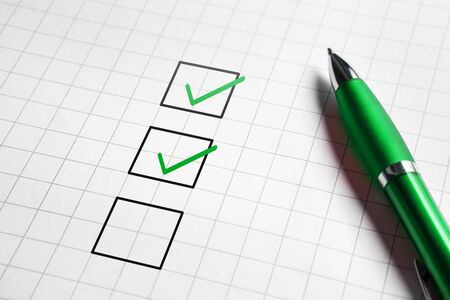 Checklist and to do list with v sign check marks in square box. Pen and paper. Project management, planning and keeping score of completed tasks concept. 스톡 콘텐츠