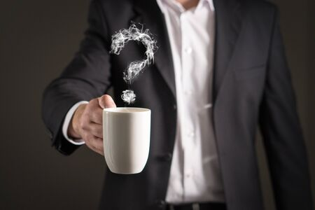 Question mark from coffee steam. Smoke forming a symbol. Business man in a suit holding a hot beverage in a mug and tea cup. Banque d'images