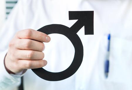 男性の健康コンセプト。男のシンボルを保持する医師。専門医または泌尿器科医。