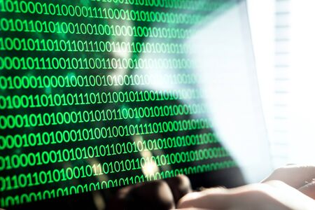 Hacker writing code with laptop computer. Binary numbers, zero and one on monitor screen. Cyber security threat, attack and online crime concept. Stock Photo