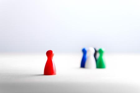 Allein sein, Außenseiter und Ausgestoßener. Konzept von Rassismus, Diskriminierung, Mobbing und sozialer Isolation. Brettspielpfandgegenstände auf Holztisch. Standard-Bild