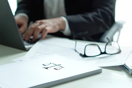 Lawyer working in office. Attorney writing a legal document with laptop computer. Glasses on table. Pile of paper with scale and justice symbol. Law firm and business concept. Banque d'images