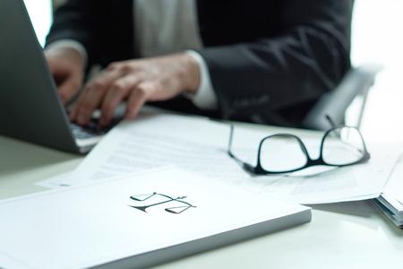 Prawnik pracujący w biurze. Adwokat piszący dokument prawny na komputerze przenośnym. Okulary na stole. Stos papieru z symbolem skali i sprawiedliwości. Kancelaria i koncepcja biznesowa.