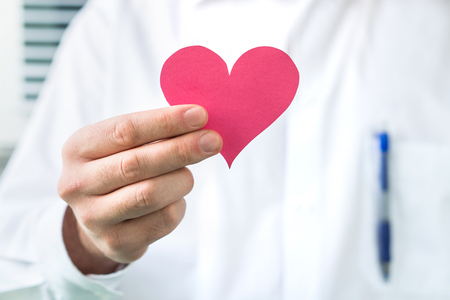 Doctor holding red heart. High blood pressure, heart attack or disease concept.