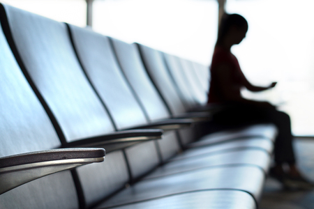 Delayed and cancelled flight concept. Silhouette woman looking her watch in airport terminal to see the time in airport waiting room and departure lounge.
