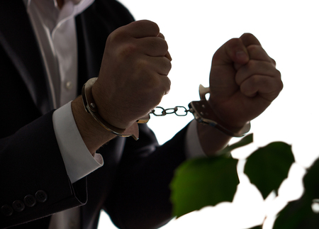 Financial fraud concept. Businessman, politician or man in a suit in handcuffs. Business criminal in shackles. Stock Photo