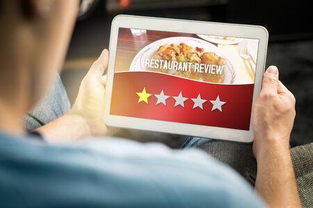 Recensione negativa del ristorante. Cliente deluso e insoddisfatto che dà una valutazione terribile con il tablet su un sito, un'applicazione o un sito Web di critica immaginaria. Uomo che dà uno su cinque stelle a casa.
