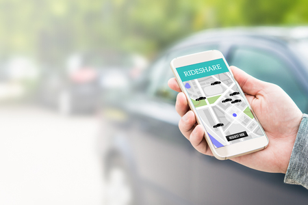 Rideshare taxi app on smartphone screen. Online ride sharing and carpool mobile application. Modern people and commuter transportation service. Man holding phone with a car in background.