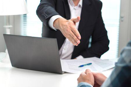 L'uomo d'affari offre e dà la mano per la stretta di mano in ufficio. Colloquio di lavoro riuscito. Richiedi un prestito in banca. Il rappresentante, il funzionario di banca o l'avvocato agitano per affare, accordo o vendita. Aumento del salario.
