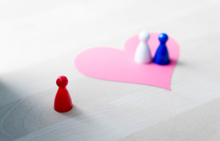 Having affair, infidelity or cheating concept. Love triangle or being third wheel. Board game pawns and paper heart on table. Stock Photo
