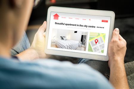 El hombre busca apartamentos y casas en línea con un dispositivo móvil. Alquiler de casas de vacaciones o sitio web o aplicación de bienes raíces. Mercado imaginario de internet para alojamiento vacacional o para encontrar un nuevo hogar.