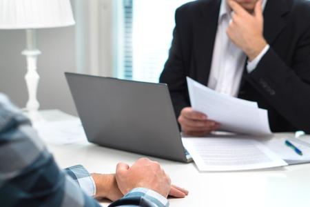 Entrevista de trabajo o reunión con el trabajador bancario en la oficina. Hombre de negocios teniendo en cuenta. Discusión sobre préstamos, hipotecas o seguros. Conversación de recursos humanos. Contratar o ser despedido. Hombre pensativo Foto de archivo