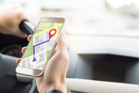 Navigation with mobile app in smartphone. Online map and GPS application on cellphone screen. Inside view in car to hand holding phone in cockpit when driving.