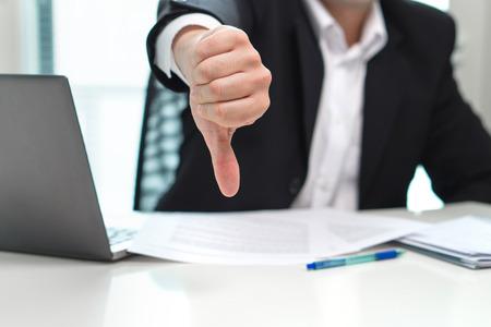 Biznes człowiek pokazuje kciuk w dół w biurze. Zdjęcie Seryjne