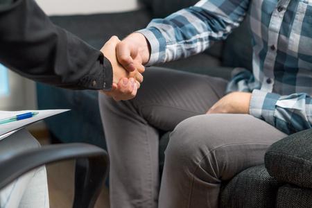 握手をする男とプロの女性。合意のための握手。面接後に採用された応募者、または不動産屋の賃貸・購入に同意した申請者。