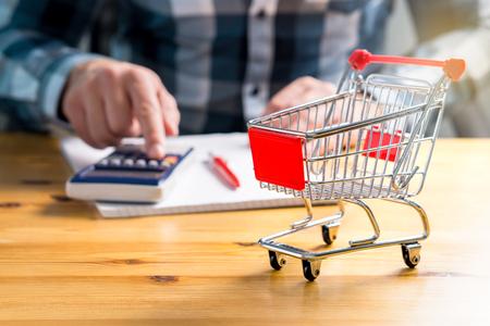 Steigende Lebensmittel- und Lebensmittelgeschäftpreise und Lebenshaltungskostenkonzept. Bemannen Sie Lebensmittel- und Konsumgütergeld mit Stift, Papier und Taschenrechner zu Hause zählen. Budget der benachteiligten und einkommensschwachen Familie.