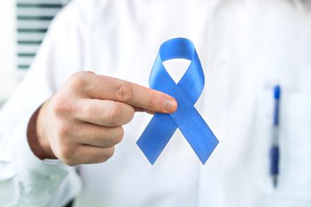 Prostate cancer awareness concept. Doctor holding blue ribbon.