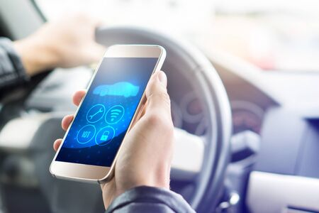 Internet of things (IOT) mobile app in smart phone for modern car. Hand holding smartphone with futuristic ADAS system. Vehicle with autonomous self control. Interior view in cockpit.