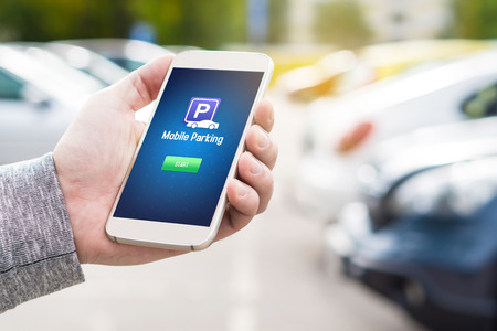 Mobile parking app on smartphone screen. Man holding smart phone with car park application in hand. Internet payment online with modern device. Row of vehicles in the background.