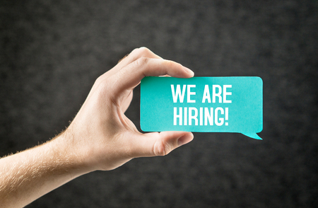 We are hiring text on speech balloon held by hand on dark background. Recruitment, human resources and employment concept. Labour wanted. Announcement for opening in creative communications agency. Stock Photo