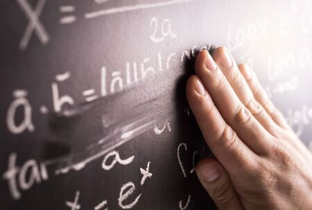 Making mistakes and wrong answer concept. Hand wiping math formula off blackboard in classroom at school. Student or teacher correcting incorrect calculation on chalkboard.