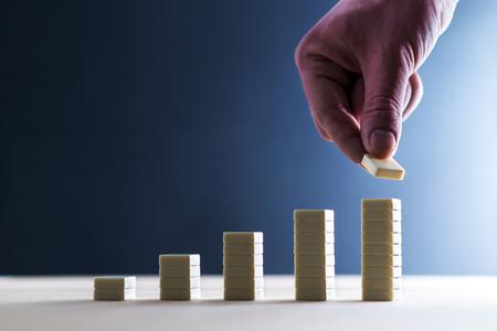 Crecimiento del negocio, éxito financiero, resultado récord o aumento en el concepto de rotación. Desarrollo, mejora y consecución de objetivos. Angel inversor haciendo inversiones y asumiendo riesgos. Mano apilando azulejos.