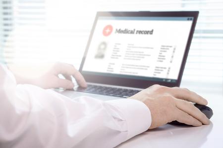 Arts die laptop en elektronisch medisch dossier (EMR) systeem gebruikt. Digitale database van patiëntenzorg en persoonlijke informatie op computerscherm. Hand op muis en typen met toetsenbord.