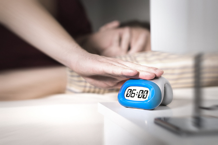 Man dont want to wake up for work in the morning. Turning off alarm clock or press snooze button with hand. Lazy person unable to get out of bed. Bad monday. Too early to get up. Stock Photo