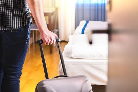 Hombre tirando de la maleta y entrando en la habitación del hotel. Viajero entrando a la habitación o caminando dentro del motel con equipaje. Concepto de alquiler de apartamentos de viajes y vacaciones.