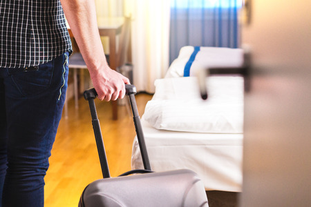 Man pulling suitcase and entering hotel room. Traveler going in to room or walking inside motel with luggage. Travel and holiday apartment rental concept.