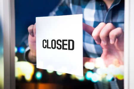 Bankruptcy, failed business going down or opening times concept. Man putting closed sign in window in cafe, restaurant, shop, store or agency. Late at night in city.