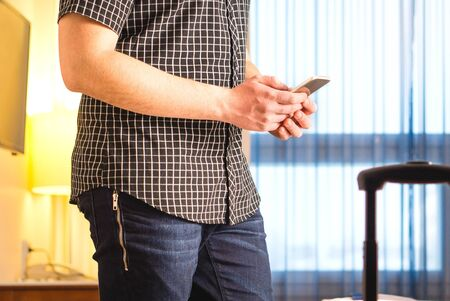 Smartphone in hotel room. Login to free hotel wifi and internet access. Traveler with mobile phone. Young man using cellphone.