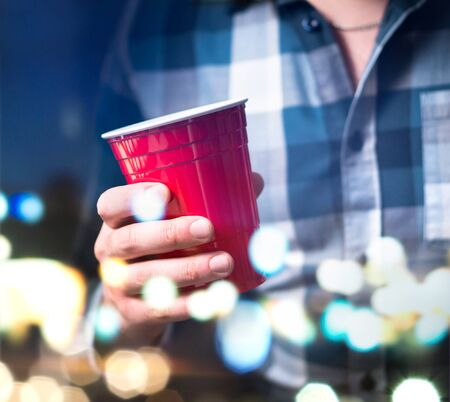 Young man holding red cup in a luxury party. Person having fun and drinking alcohol. Abstract and modern celebration concept. Stock Photo