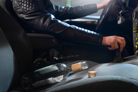 Drunk driving concept. Young man driving car under the influence of alcohol. Empty bottle of wine on front seat. Going away from party late at night. Traffic safety risk.