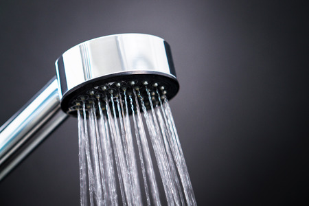 Close up of shower head against dark black background. Water running from faucet in modern bathroom. Stock Photo - 95967491