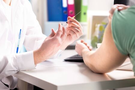 Doctor giving patient vaccine, flu or influenza shot or taking blood test with needle. Medicine, insulin or vaccination. Nurse with injection or syringe. Hospital office room.