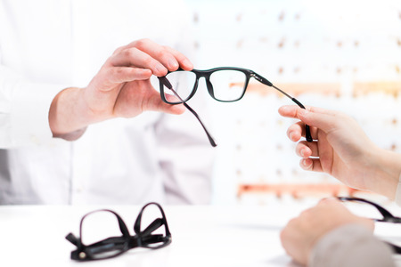 Optician giving new glasses to customer for testing and trying. Eye doctor with client comparing spectacles and choosing lenses in store.