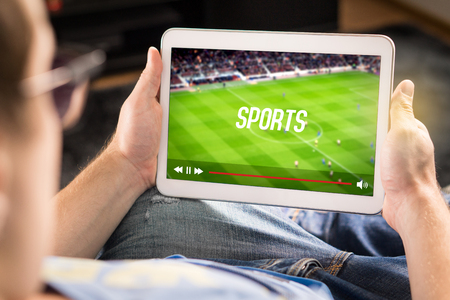 Man watching sports on tablet. Football and soccer game live stream and video player on screen. Pay per view (PPV) service. Replay or highlights broadcast. Lazy person relaxing. Couch potato.