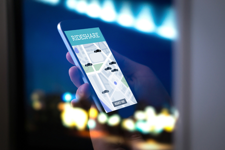 Ride sharing and carpool mobile application. Rideshare taxi app on smartphone screen. Modern online people and commuter transportation service. Man holding phone late at night. City street lights.