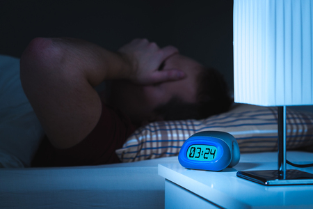 Insomnia and sleepless concept. Man unable to sleep. Exhausted and tired. Covering face with hand. Alarm clock on nightstand and bed in bedroom.