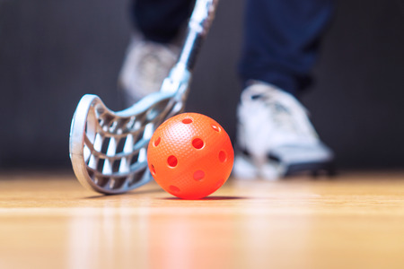 Floorball player with stick and ball. Floor hockey concept.