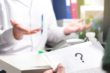 Medical problem. Patient reading health care document with question mark. New or unknown disease. Can't find or no cure for illness. Wrong diagnosis. Clueless doctor spreading hands. Stockfoto