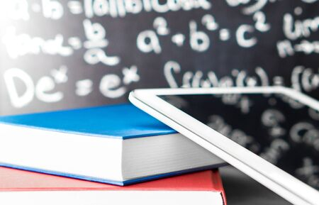 E learning and modern education concept. Smart mobile device and tablet with stack of colorful books in front of a blackboard in school. Studying on internet or teaching online. Digital book reader. 스톡 콘텐츠