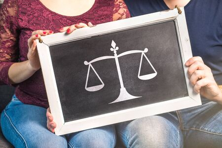 Law, marriage, relationship, legal advice or prenuptial agreement concept. Session with divorce lawyer or attorney. Couple, man and woman, holding blackboard with scale symbol. Stok Fotoğraf