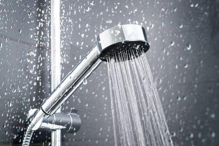 Ducha fresca detrás de la ventana de vidrio mojado con salpicaduras de gotas de agua. El agua de la alcachofa de la ducha y el grifo del baño moderno