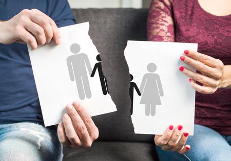 Trennung, Scheidung, gemeinsames Sorgerecht für Kinder und Trennung von Familien. Schlechte Erziehung. Rechtsstreit um Kinder. Paare, die ein Papier mit Mann-, Frauen- und Kinderikone zerreißen.
