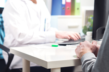 Doctor and patient in appointment, visit or meeting in hospital office or emergency room. Physician or nurse writing prescription, instructions, medical record or data with computer.