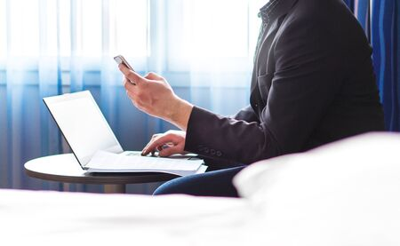 Business man in hotel room with smartphone and laptop. Businessman reading emails or using social media. Remote work during business trip. Making phone call. Elegant man in suit using hotel wifi.
