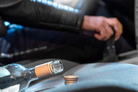 Betrunkenes Fahrkonzept. Junger Mann, der Auto unter dem Einfluss des Alkohols fährt. Hand auf Schalthebel. Nahaufnahme einer leeren Flasche Wein auf dem Vordersitz. Verkehrssicherheitsrisiko.